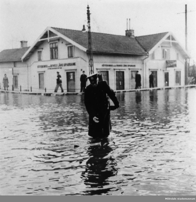 Uniformsklädd man (Polisman) under tjänstgöring vid översvämning på Göteborgsvägen i Mölndalsbro. Göteborgs- och Bohusläns sparbank syns i bakgrunden. Omkring 1920