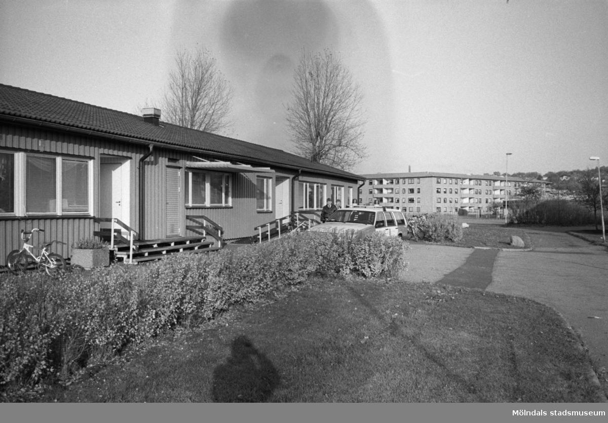 En utomhusbild på enplanshuset Katrinebergs daghem. Utanför entrén har någon parkerat en cykel. Längre bort står en man bredvid en Volvo kombi. I bakgrunden ser man Åbyområdets fyravåningshus med lägenheter.