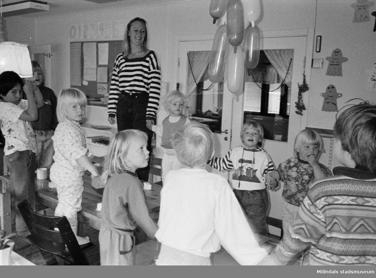 Flertalet barn och förskollärare Britt Johansson står på stolarna runt ett bord i köket. Några håller varandra i händerna. På bordet finns kaffekoppar och fat med bakverk/tårta på. I taket hänger uppblåsta ballonger. På väggen bakom hänger uppklistrade Spöket Laban-figurer som barnen har gjort. Hoppetossan, Katrinebergs daghem 1992.