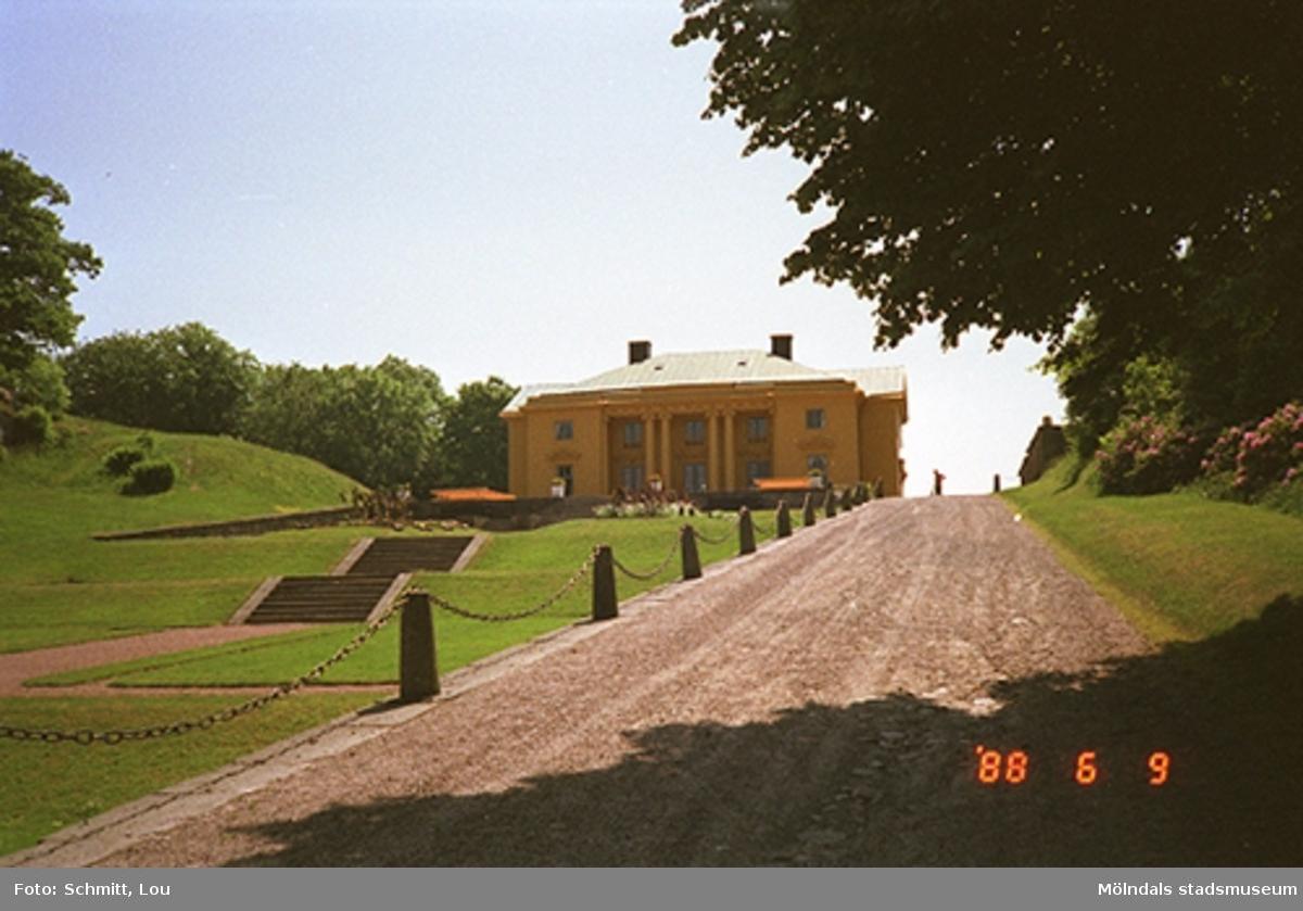 En vacker sommardag i juni 1988 på Gunnebo slotts framsida, sett från lite längre avstånd. Till vänster ser man trappor mellan gräsmattorna. Till höger går en grusväg, kantad av solpar, upp till slottet.