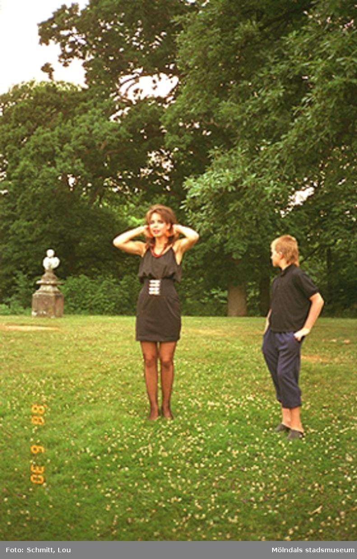 En ung dam och en tonårspojke står på en gräsmatta i Gunnebo slottspark. I bakgrunden skymtar man en skulptur.