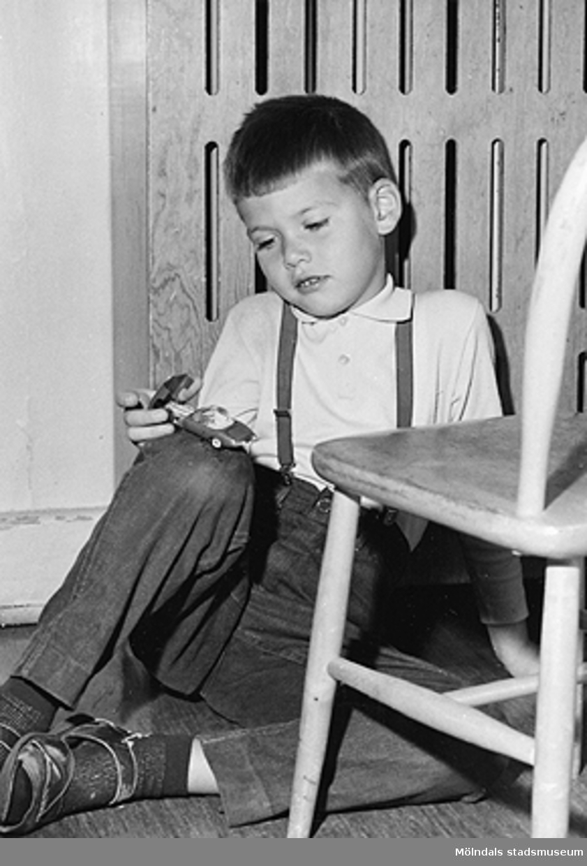 En pojke sitter på golvet hållandes en leksaksbil i handen. Holtermanska daghemmet 1953.