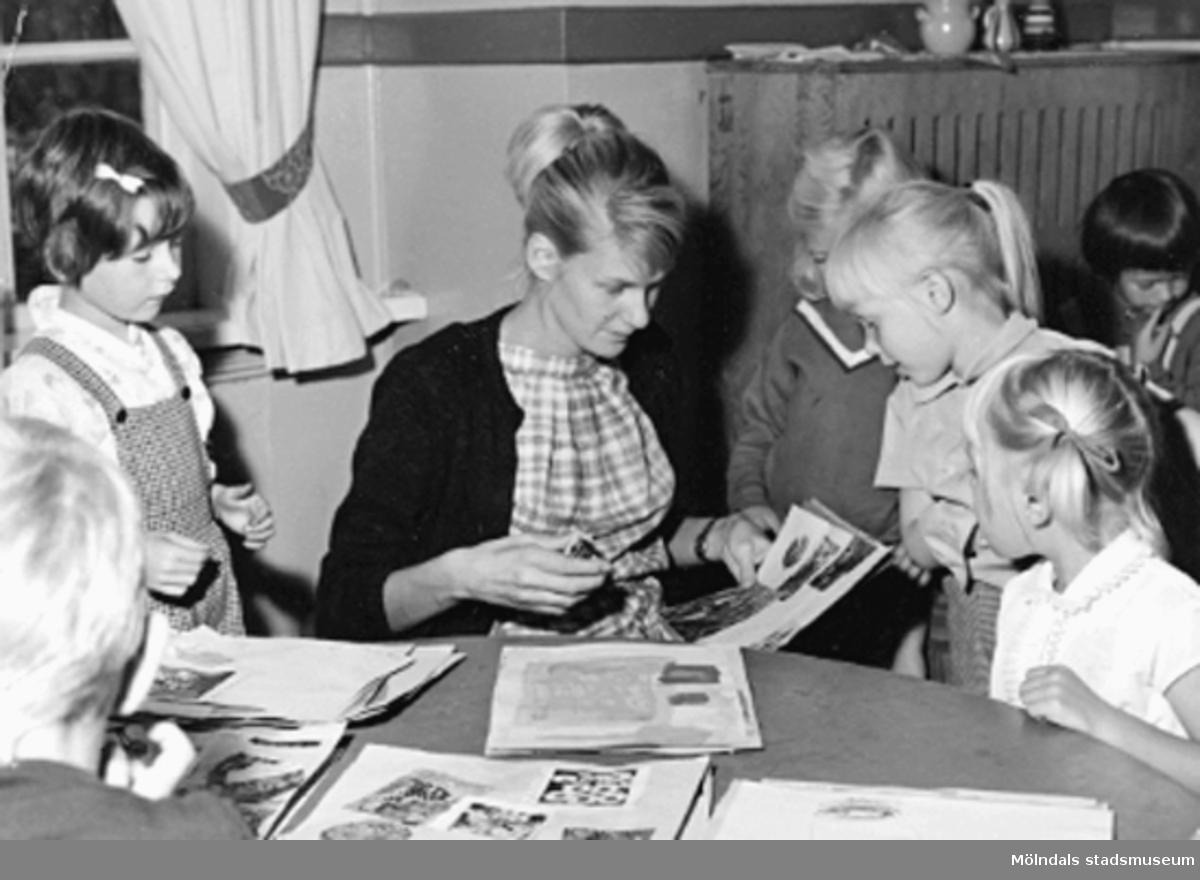 En lärarinna och några barn pysslar vid ett bord. Holtermanska daghemmet 1953.