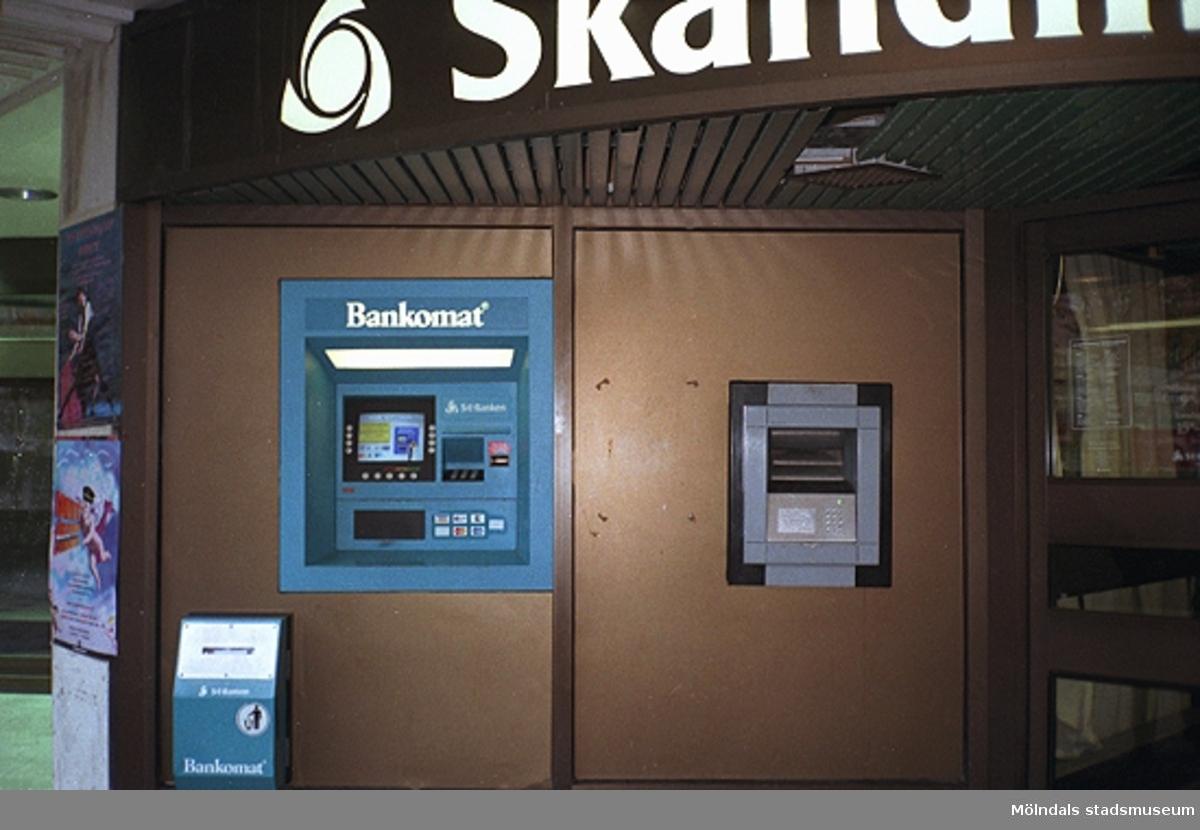 Bankomat utanför Skandinaviska Enskilda Banken på Brogatan/Nygatan. Mölndalsbro i dag - ett skolpedagogiskt dokumentationsprojekt på Mölndals museum under oktober 1996. 1996_1212-1226 är gjorda av högstadieelever från Kvarnbyskolan 9D, grupp 5. Se även 1996_0913-0940.