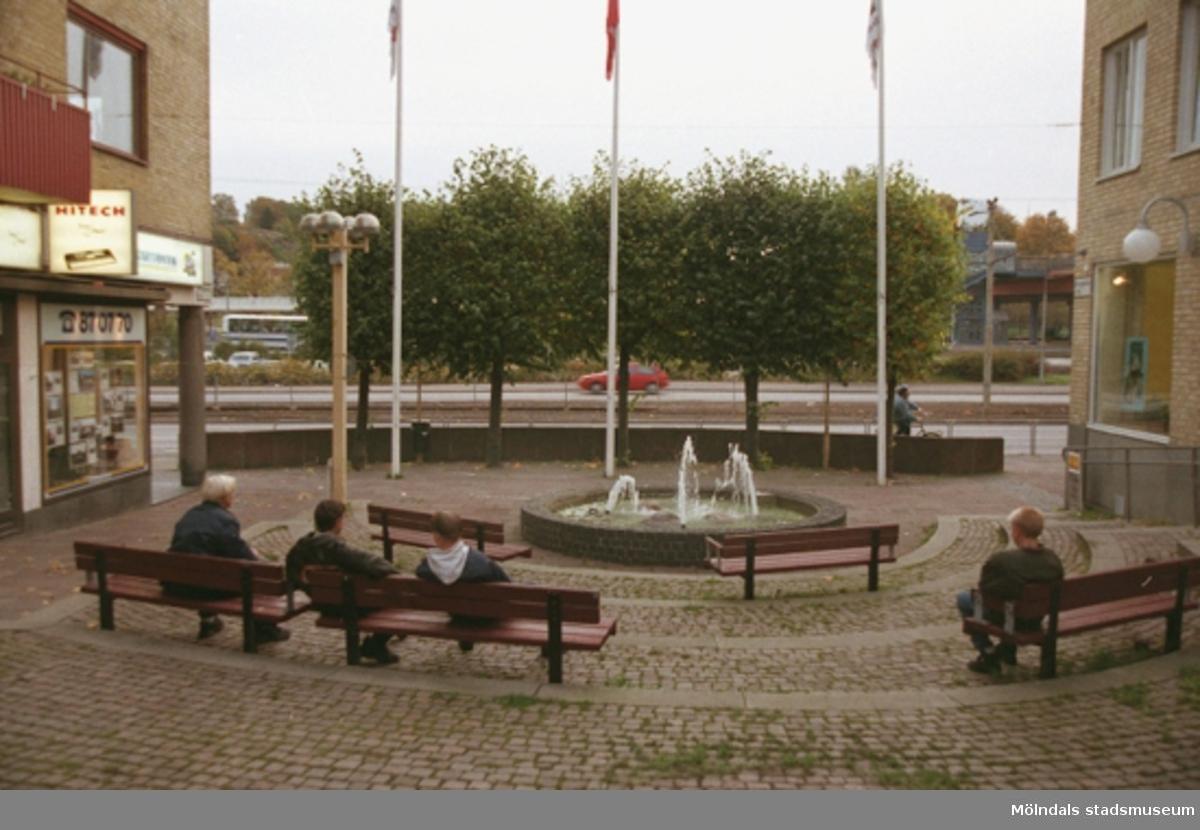 Personer sitter på bänkar i början av Brogatan. Göteborgsvägen passerar i bakgrunden. Mölndalsbro i dag - ett skolpedagogiskt dokumentationsprojekt på Mölndals museum under oktober 1996. 1996_1246-1263 är gjorda av högstadieelever från Åbyskolan 8A, grupp 1. Se även 1996_0913-0940.