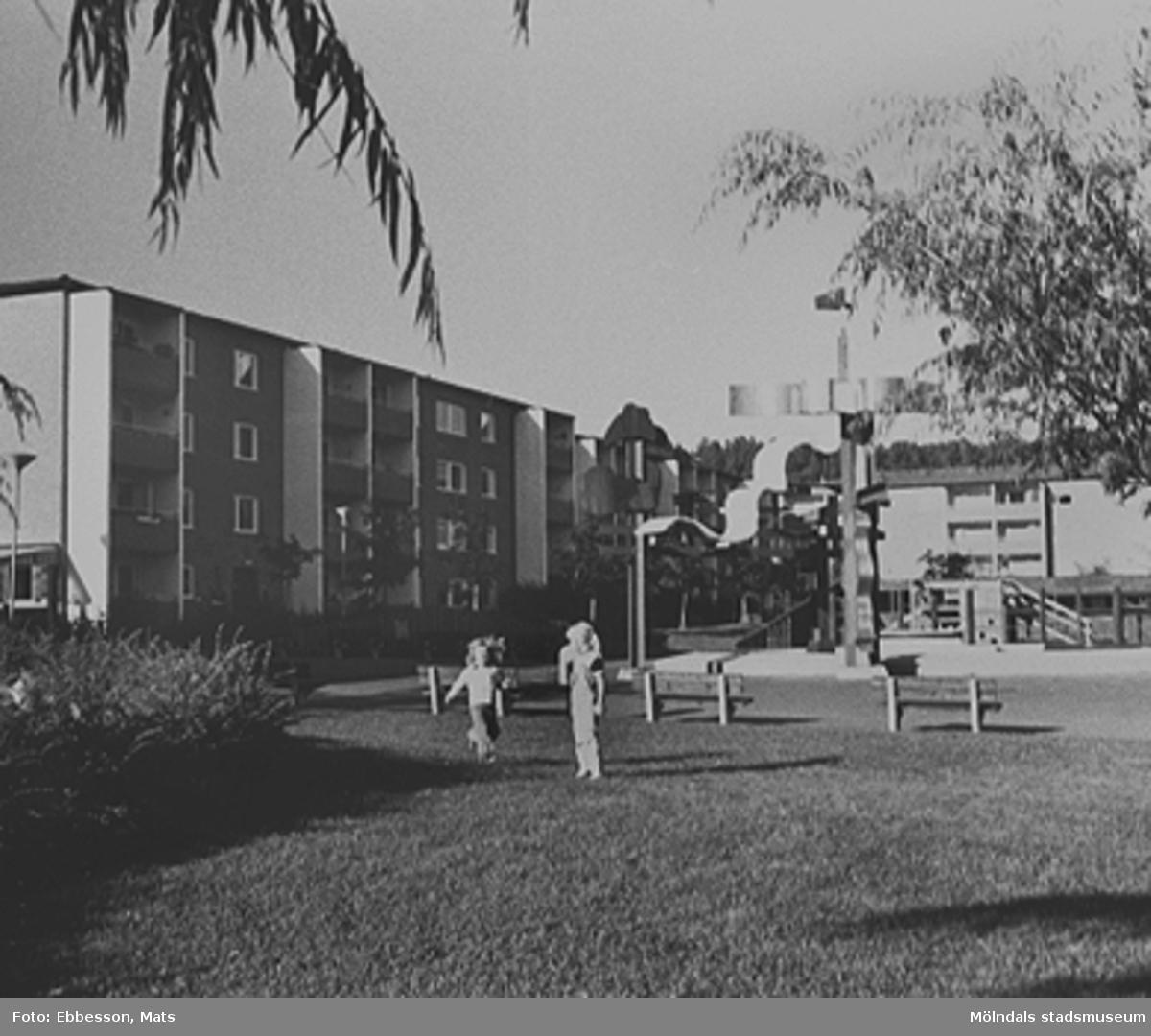 """Till höger syns ett runt betongfundament på Kvarteret Rullharvens gård, 1980-tal. I dess vatten brukade barnen bada på somrarna. Här fanns också en fontän med namnet """"Bifrost"""". Det var ett vattenspel som gav alla regnbågens färger när ljuset bröt vattnet. Fundamentet blev senare en plantering."""