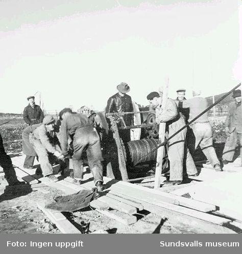 Uppvinschning för hand av radiomast. Enligt uppgift visar fotografiet arbetet med resningen av den provisoriska fackverksmasten vid rundradiostationen i Ljustadalen, 1948. Enligt en annan uppgift visar fotografiet arbetet med radiomasterna i Brattåsen utanför Östersund, Jämtland.