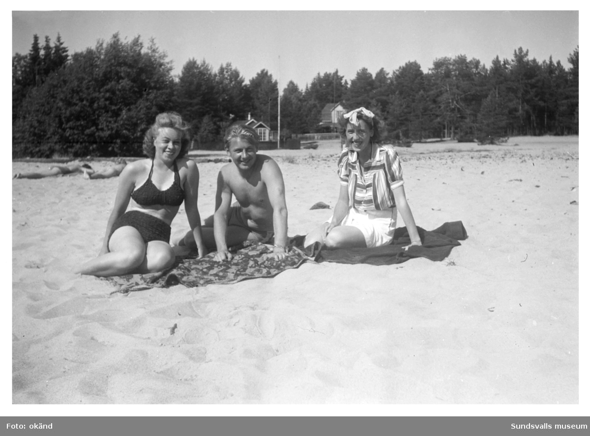 Sandstranden vid Tranvikens sommarstugeområde. Tre okända badgäster i förgrunden. I bakgrunden syns Kamels (t.v) och Liljeholms (t.h.) stugor.