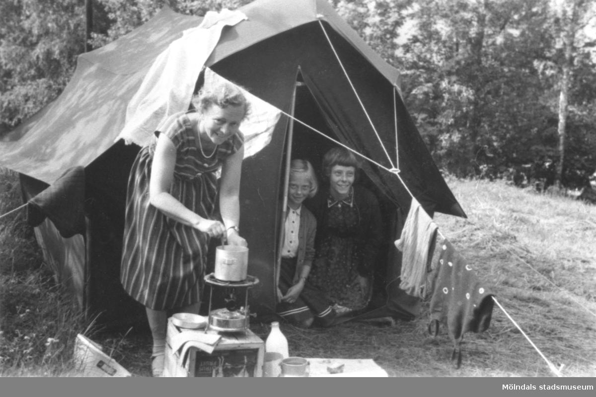 Rosa Pettersson och döttrarna Karin och Eva Pettersson på tältsemester i Dalarna 1957. Mamma Rosa lagar mat på ett Primuskök.