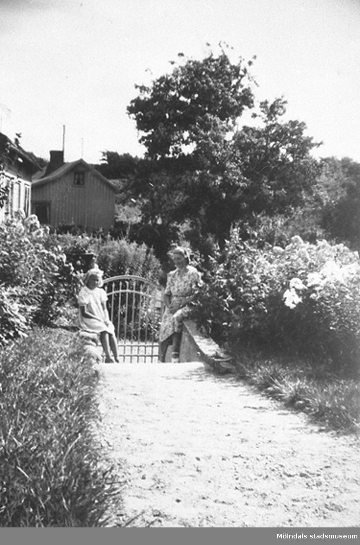 Ett barn och en kvinna står vid en grind i en trädgård.Sommar i Lindome i början av 1940-talet.