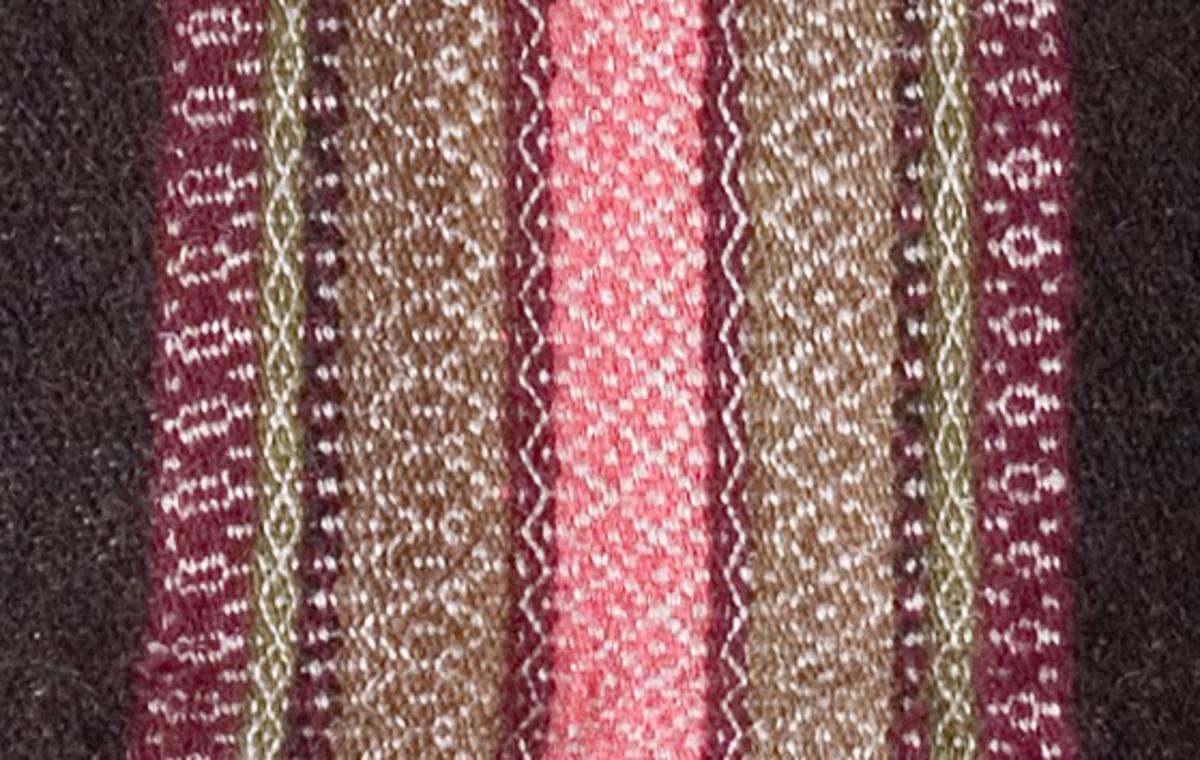 Täcke i rosengång med tre skaft. Materialet handspunnet och växtfärgat. Garn: varp av lingarn. Inslag: Ränder av svart nöthårsgarn av ko och gethår samt ull. Andra ränder av rosa, grönt och lila ullgarn. Två våder ihopsydda.