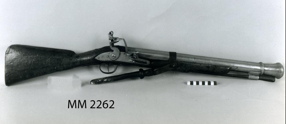 """Muskedunder, nicka, att nyttja på galérer. Flintlås. Trombonpipan av metall, vidgas åt mynningen. (Kanonmynning) Stock och kolv av trä, mekanismen av järn. På låset är instämplat """"Wilson"""". Kaliber: 40 mm. 1700-talet. Pipans längd 560 mm. Enligt 1761 års inv. en uppfinning av Cap.Lieut. Gyllenhök."""