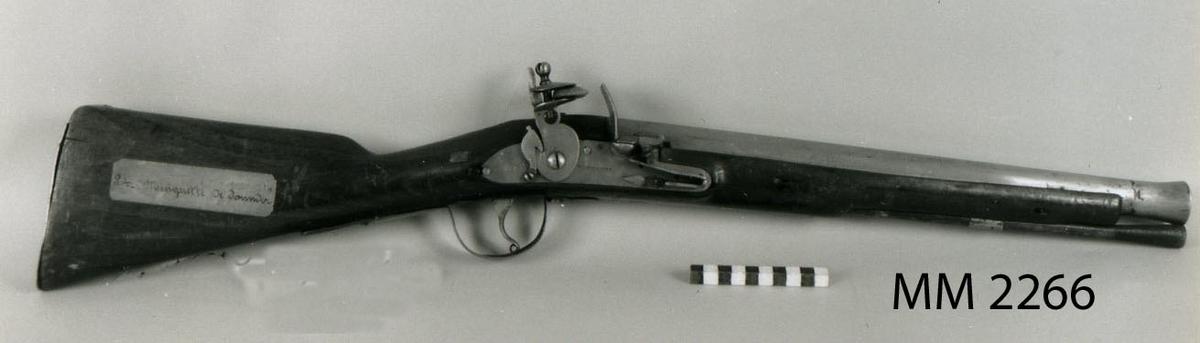 """Muskedunder, mindre, med trumpetformad järnpipa och flintlås. Holländsk, 1700-talets förra hälft. Beslagen av järn. Stock och kolv av trä. Bakbeslagen av mässing. Låset stämplat : """"Buckmaster"""". Finns upptagen på 1761 års inventarium. Pipans längd 447 mm."""