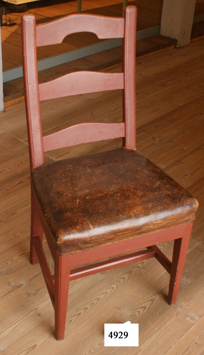 Stol av trä, målad i gulbrunt. Ryggstödet försett med tre stöd, varav det översta har urtag i underkant. Fyrsidiga ben sammanhållna med tre fyrsidiga slåar. Sitsen klädd med ryssläder.