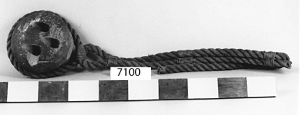 Jungfru av trä. Cylindrisk med avrundade kanter och utvändigt försedd med spår för trossens fastsättande till relingen eller däck. Från sida till sida genomborrad med tre hål för fasättning till vanten. Svartmålad.