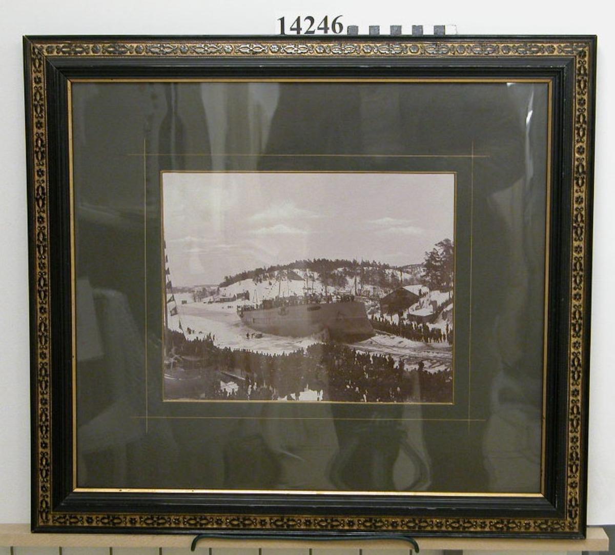 Fotografi inom glas och ram. Motiv: Pansarbåten Thules sjösättning. Text på baksidan: Pansarbåten Thules aflöpning vid Finnboda Slip d 4 Mars 1893.