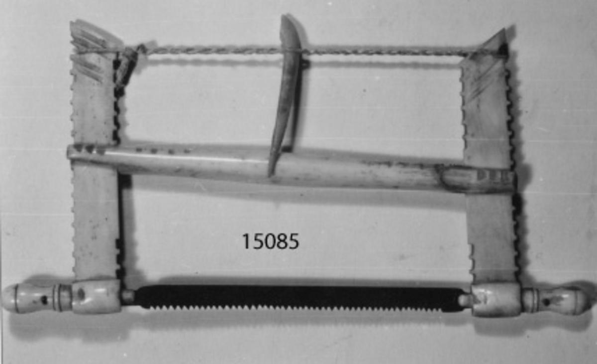 Scrimshaw (modell av såg) omålad. Sjömansarbete i den i form av en ryggsåg. Sågen är omålad och försedd med diverse olika utskärningar.