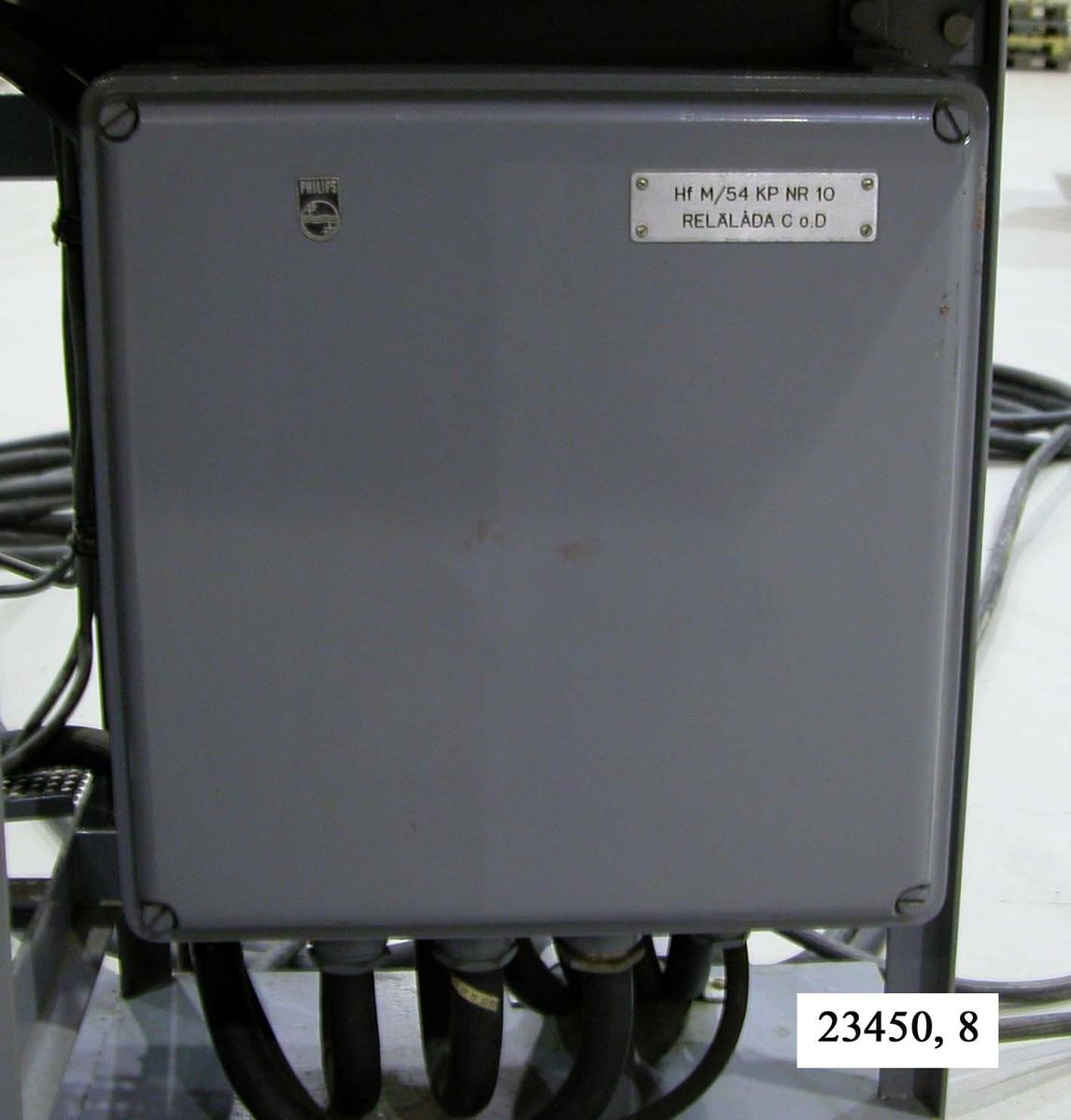 """Rektangulär, grålackerad, slät box av metall. I respektive hörn sitter bultar. I relälådans högra hörn sitter en metallbricka försedd med texten """"Hf M/54 KP NR 10, RELÄLÅDA C o. D"""". I relälådans underdel sitter ett antal kablar fästa. Relälådan är monterad på ett hydrofonstativ, nere till höger på stativets framsida.  Not: Kablaget ej medräknat i dimensioner."""