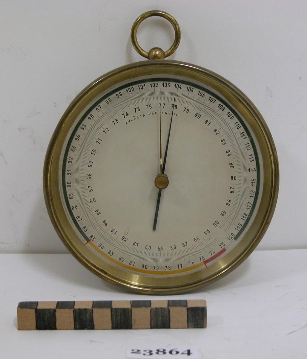 """Barometer i ett hölje av mässing. På ovansidan finns en ring för upphängning. På barometerns baksida finns den stansade texten 10/1952 tillsammans med tre kronor och numret 162. På baksidans mitt finns initialerna """"PHBN"""" inom en cirkel. Barometern är ytterst graderad 73-120, innerst är den graderad 55-90. Mellan graderna 85 och 120 går en grön, målad rand. Mellan 75 och 85 går en gul, målad rand. Mellan 73 och 73 går en röd, målad rand. På tavlan finns texten """"AVLÄSTA VÄRDEN X 10"""". Barometern har en svart visare och en inställbar löpare av mässing."""