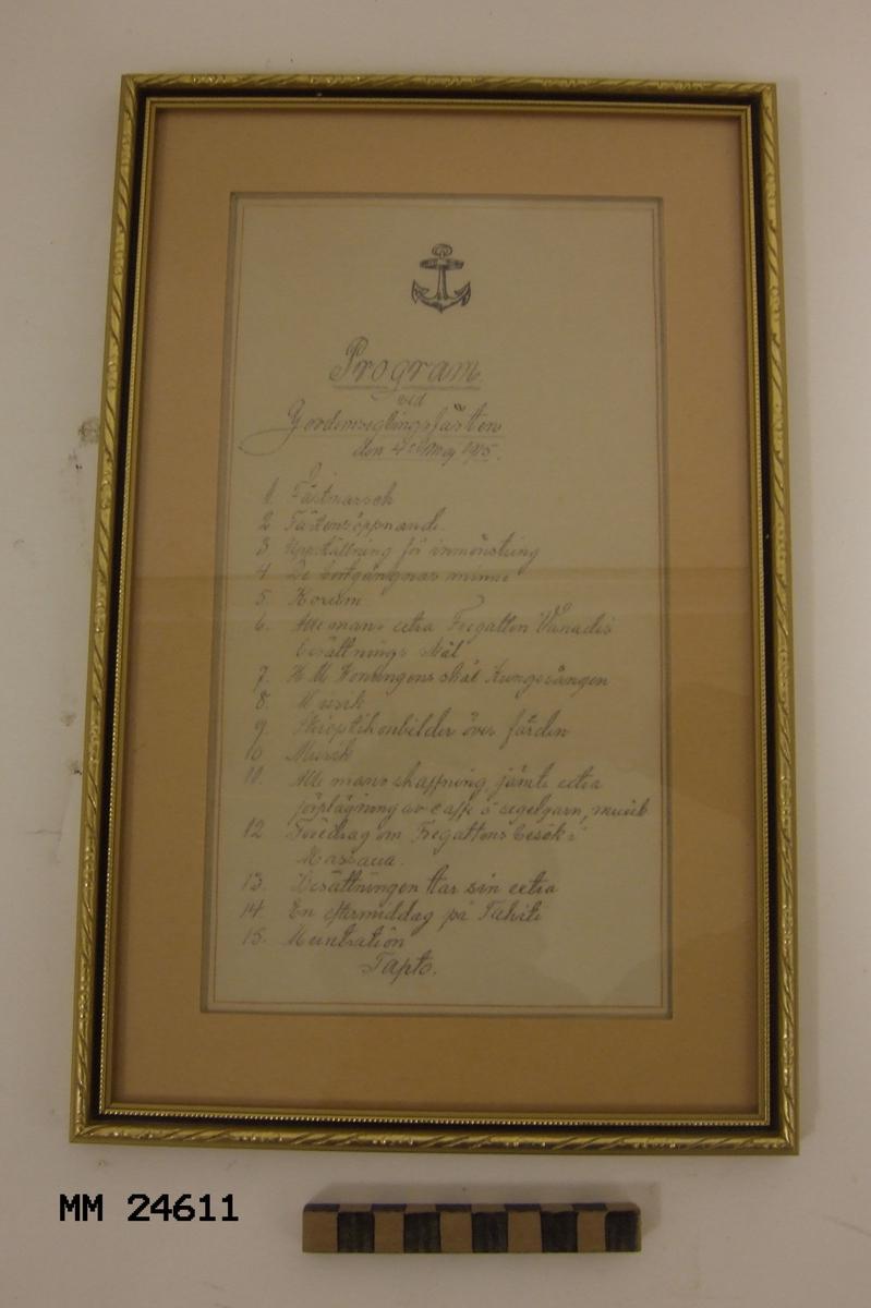 """Tavla med programmet från Jordomseglingsfesten med fregatten HMS Vanadis 1915 prydligt inramat. Rubriken på programmet lyder: """"Program vid Jordomseglingsfesten den 4 maj 1915"""". Därefter följer: """"1. Festmarsch 2. Festens öppnande 3. Uppställning för inmönstring 4. De bortgångnas minne 5. Korum 6. Alle mans extra. Fregatten Vanadis besättnings skål 7. H. M. Konungens skål Kungssången 8. Musik 9. Skioptikonbilder över färden 10. Musik 11. Alle mans skaffning 12. Föredrag om Fregattens besök i Massava 13. Besättningen tar sin extra 14. En eftermiddag på Tahiti 15. Muntration Tapto"""""""