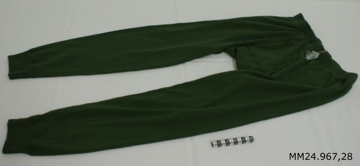 """Långkalsong modell 1991. Grön kanalstickad långkalsong av polyester, bomull och cordelan. Resår i midjan samt omlottöppning vid gylfen. Kanalstickningen gör att en luftspalt till huden skapas vilket gör att fukten inte kommer när huden. Vitlapp på insidan med kronstämpel, M-nummer, tvättråd, årtalet 2000, storlek 4, vikt 60-70 kg samt texten: """"Eiser Trikå Ab, tillverkad i Estland""""."""
