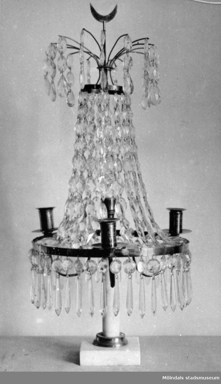 Gustaviansk lyster med slipade kristallprismor och marmorsockel med plats för fyra ljus. Gunnebo slott, 1930-tal.