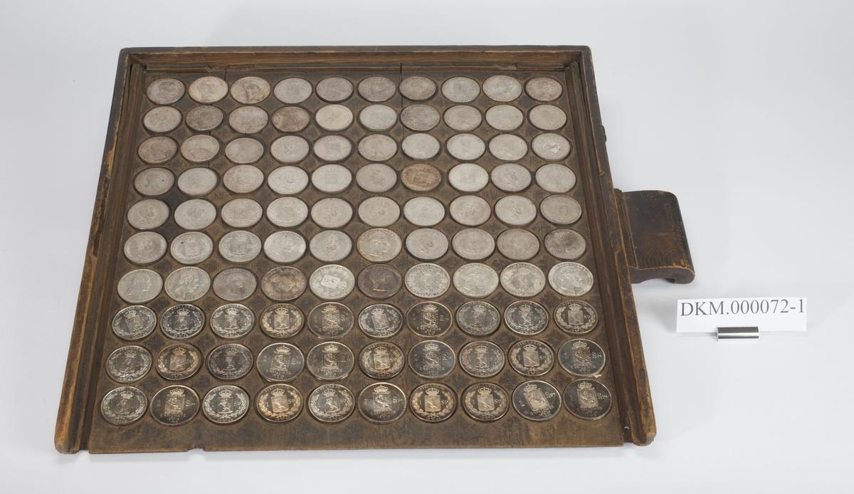 Kvadratisk brett med lave kanter på tre av sidene og ett lite rektangulært håndtak. Det er skåret ut 100 grunne hull til plassering av mynt. En labank er felt inn på tvers under brettet.