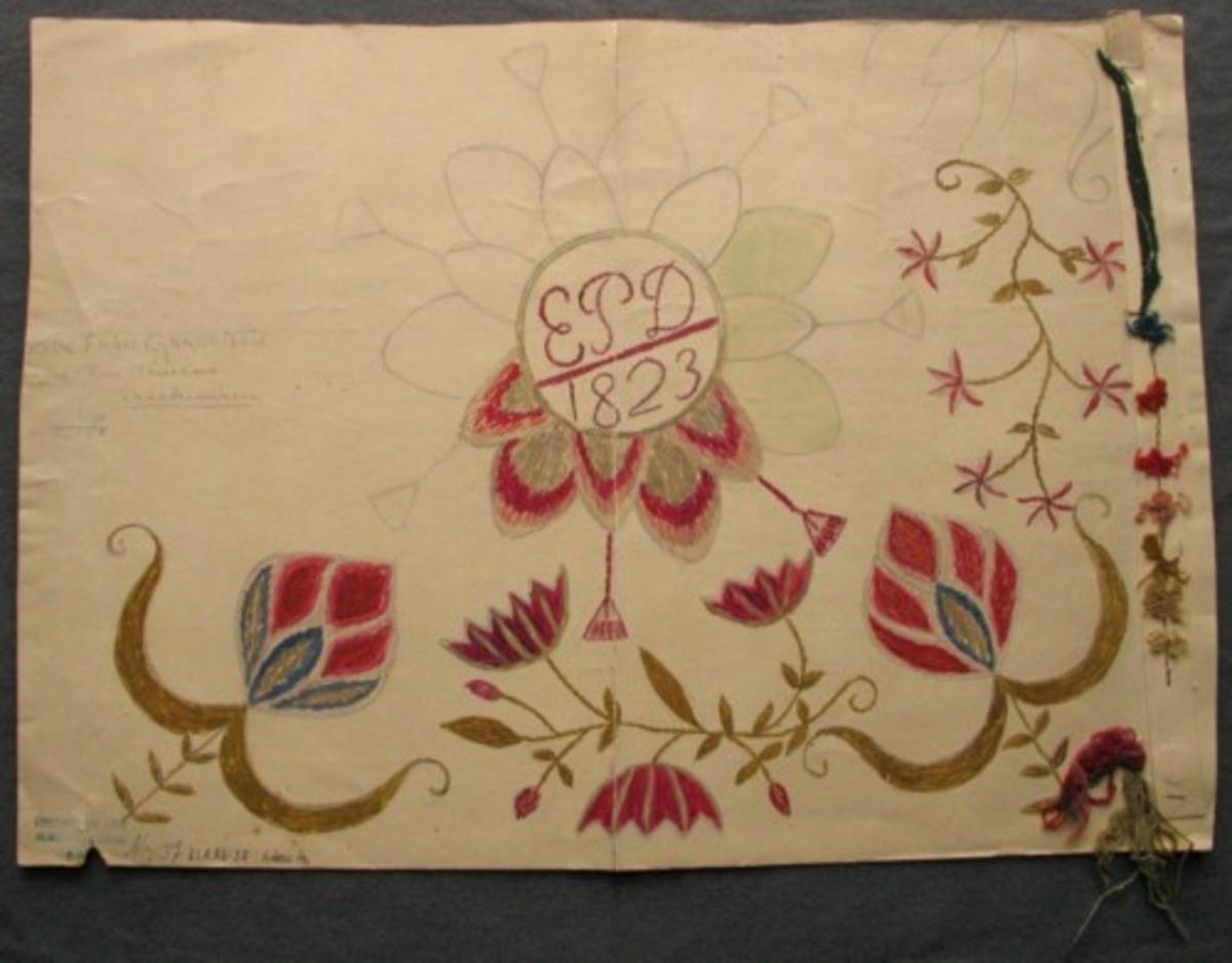 """Skiss målad på styvt papper. Del av kudde. I mitten en stor flikbladig blomma med kvastar. Monogram i mitten- EPD 1823. I hörnen stiliserade blommor, mellan dem två olika blommor på kvist. Garnprover och ett mörkgrönt tygprov  monterat i kanten. Gammal märkning och text:"""" Nr 37. Kudde från Gärds H.d  Ägare Fru Månsson, Skälderviken."""""""