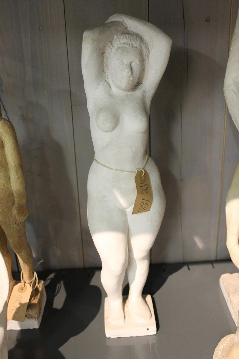 Skulptur i gips av en kvinne med hendene i kryss oppe på hode.