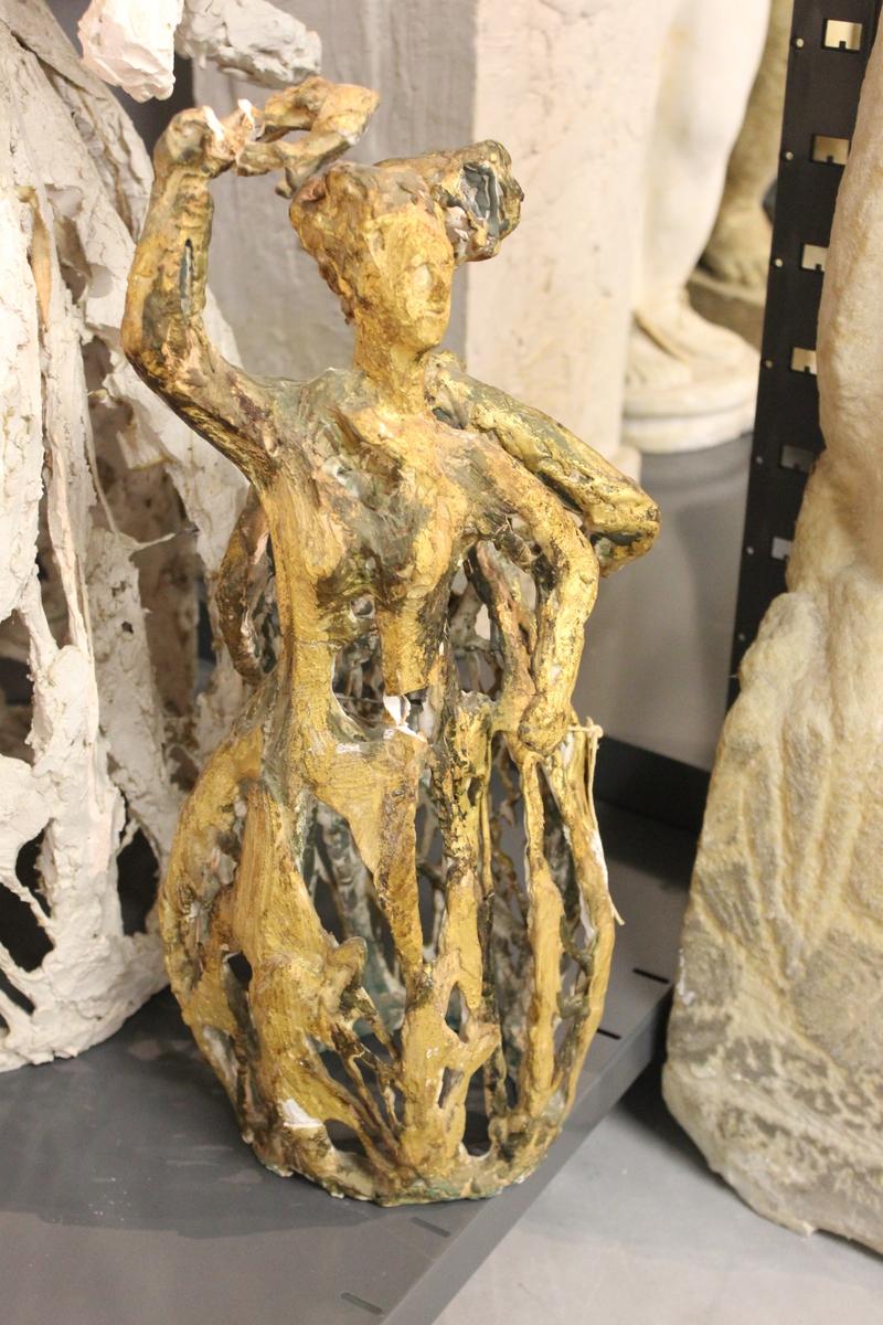 """Skulptur forgyldt gips av en kvinne med en arm over hode. Utkast til """"Haldensøylen"""". Søyle i stål. Se også nr.021, nr.213 og nr.214. Haldensøylen ble laget til byens 300-års jubileum 1965."""