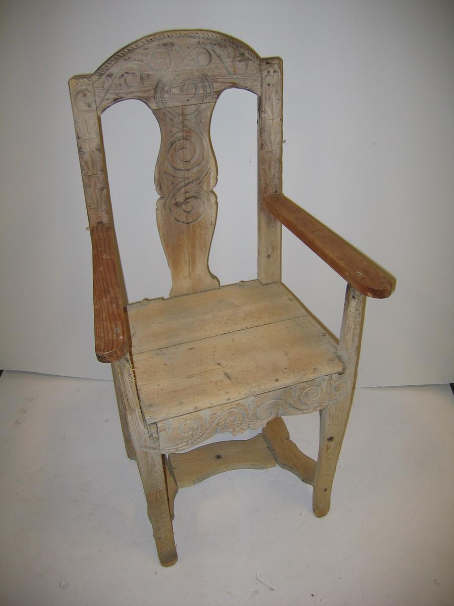 1 utskaaren stol.  En armstol av furu med rygbrett. Armene nu borte. Stolen, der er bondearbeide, er forsirt med slyngornamentik. Gave fra gaardbr. Hans Bugge, Urnæs.