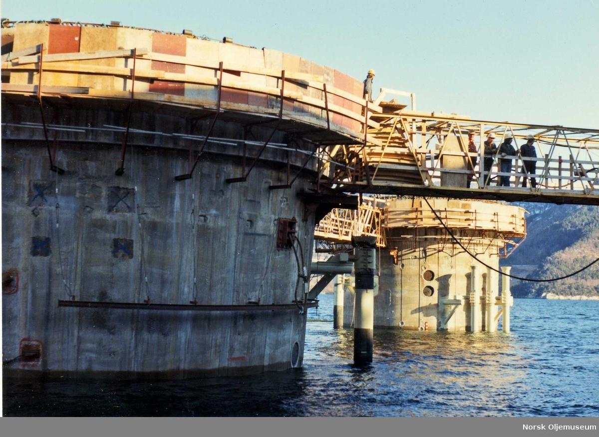 Bygging av TCP2 i Åndalsnes.  Ferdiggjøring av betongstrukturen foretas før dekk og understell kan koples sammen. Platformen er nå 121,2m under navnivå, mens søylene stikker 8,50m over vannflaten.