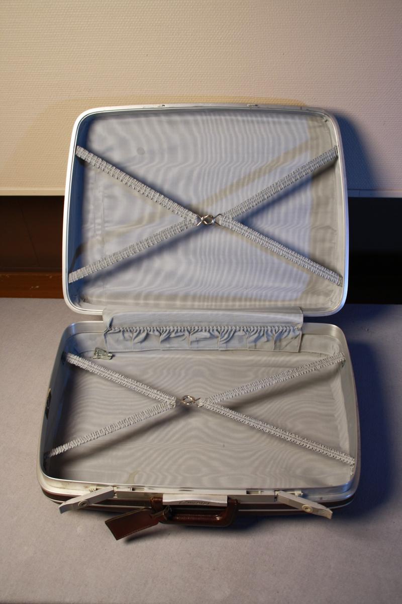 Fin koffert, skinntrukken(?). Handtak og to låsar. Festestropper og små oppbevaringslommer inni. Innsida er trukken med stoff.