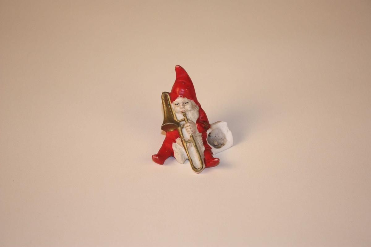 Nisse som sit og spelar trekkbasun. Ved sida av har han ei bøtte som det kan settast juletrelys i. Nissen har langt skjegg og hue med spiss.