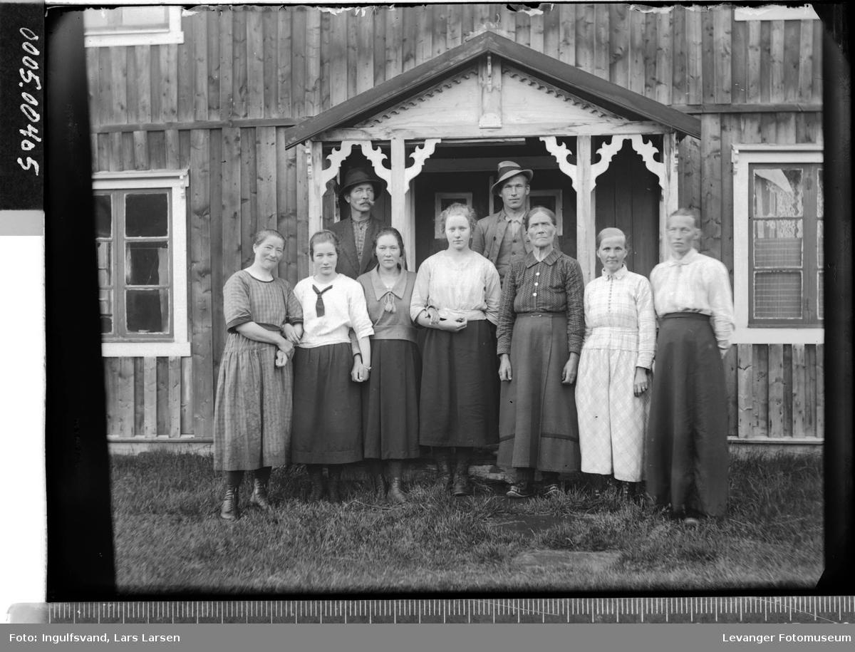 Gruppebilde av syv kvinner og to menn i en inngangsportal.