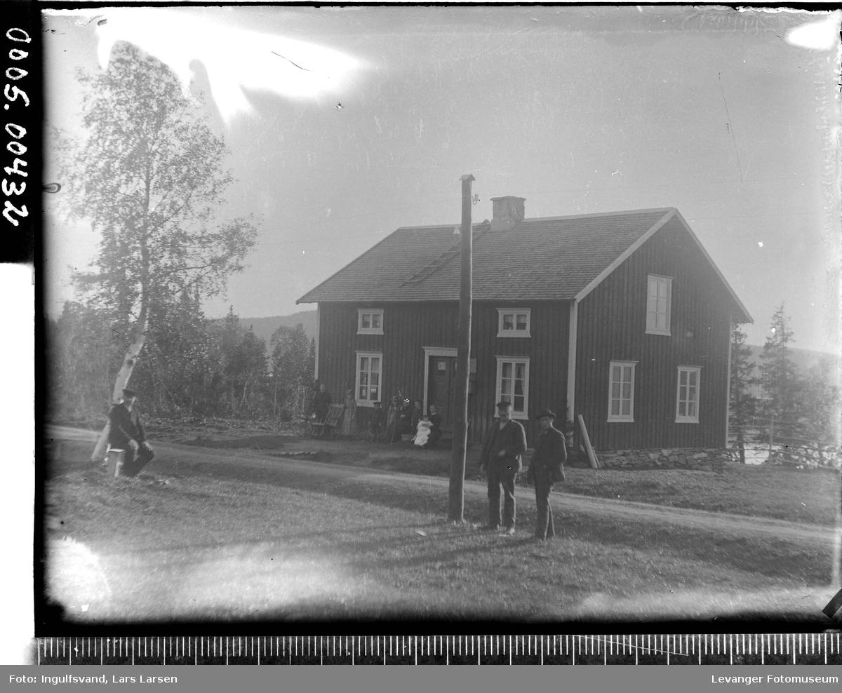 Bilde av bolighus med telefonstolpe og noen mennesker i forgrunnen,