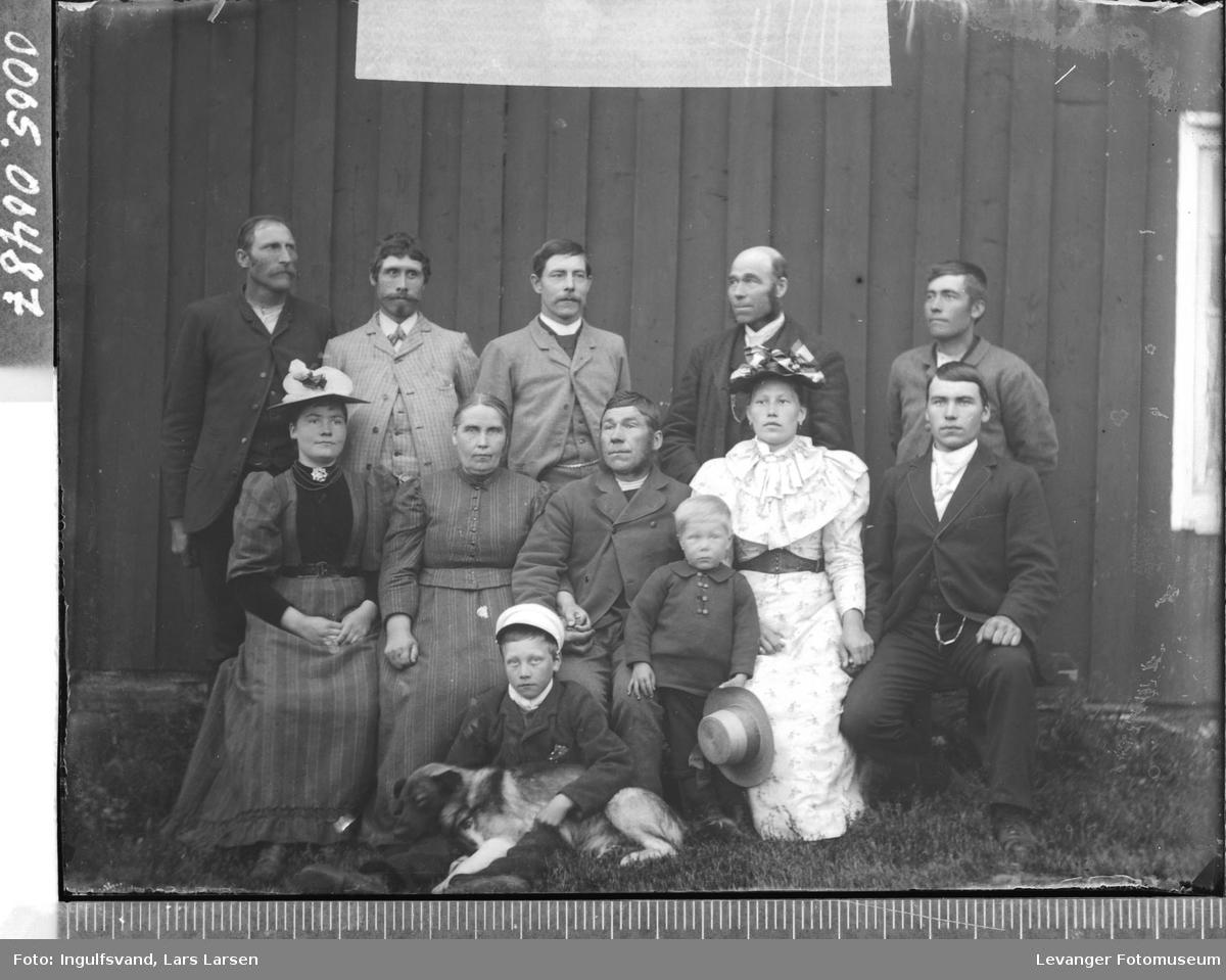 Gruppebilde med  syv menn, tre kvinner, to barn og en hund.