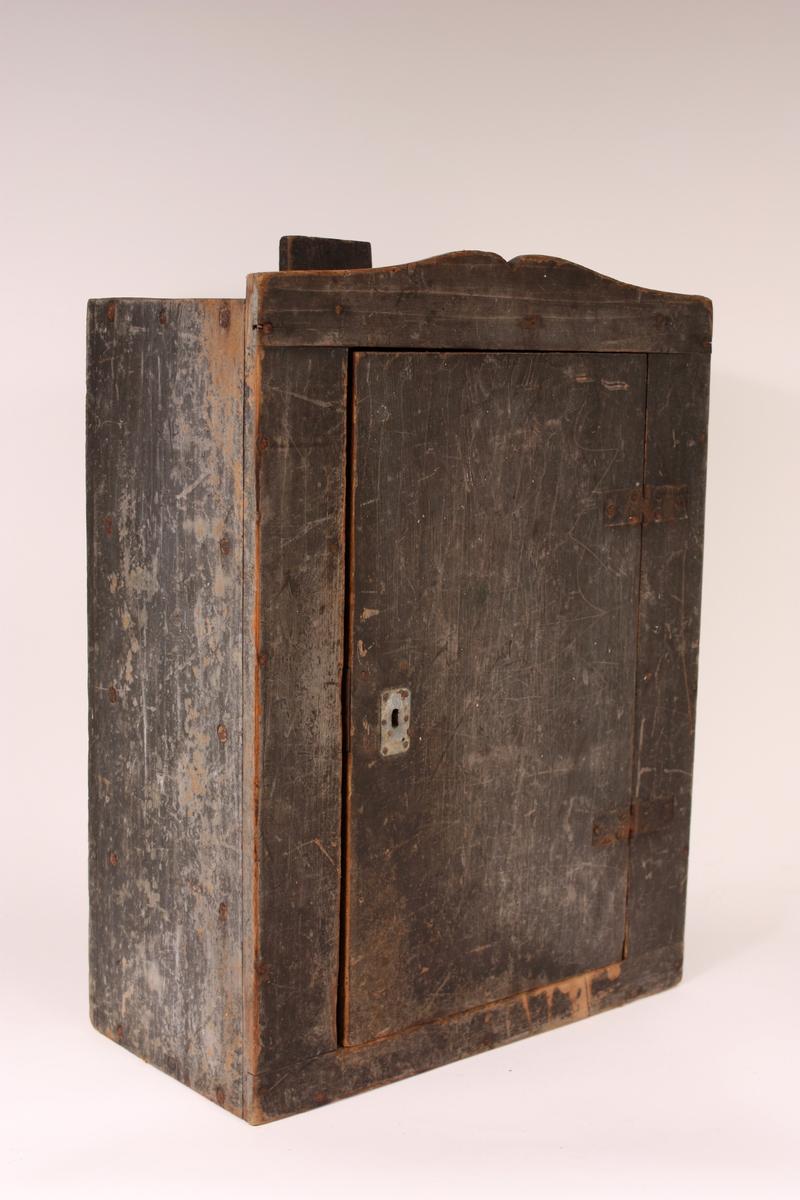 Lite rektangulært veggskap for flat bakvegg med tre hyller og låsbar dør. Gesims over døra med profilskorent overkant.