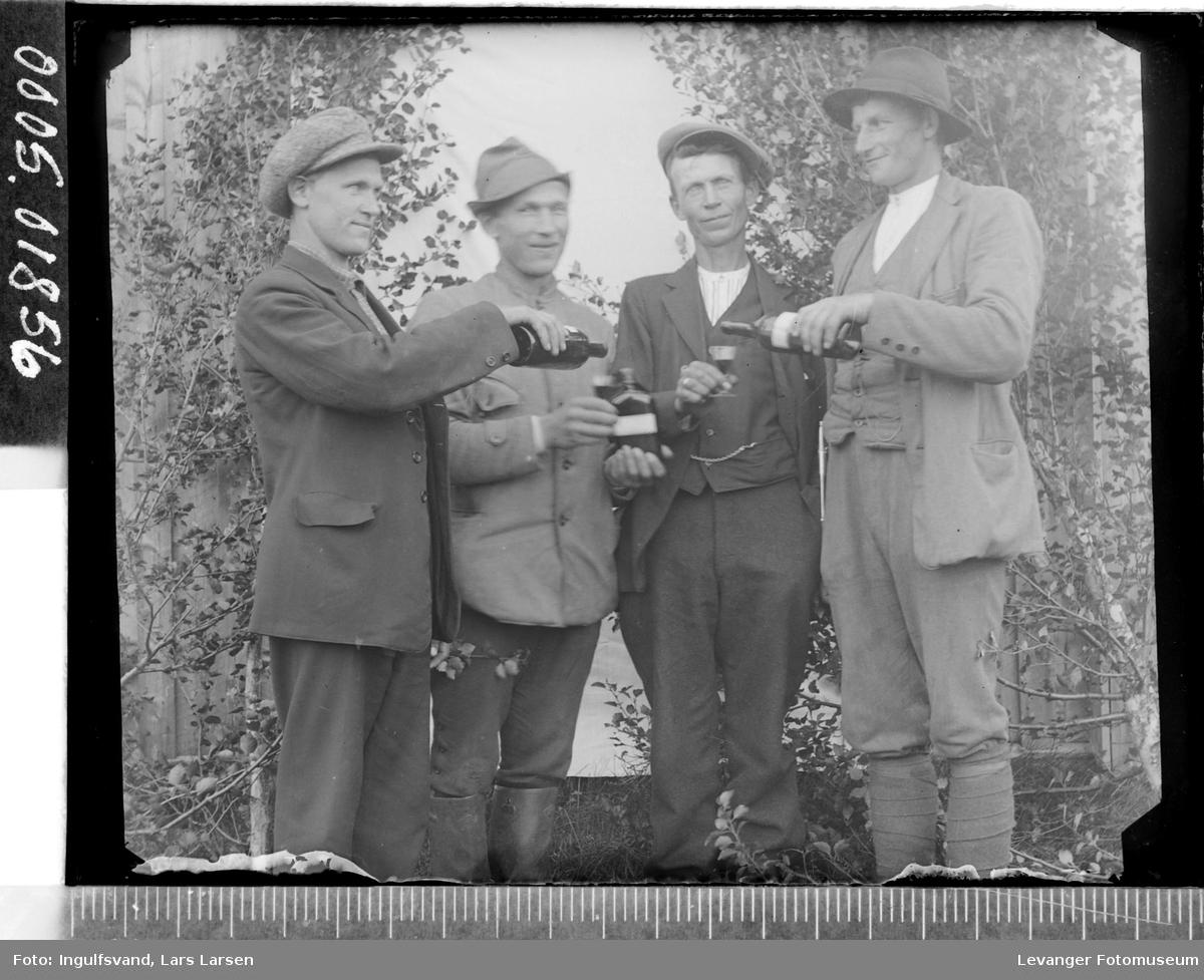 Gruppebilde av fire menn som har et drikkelag.