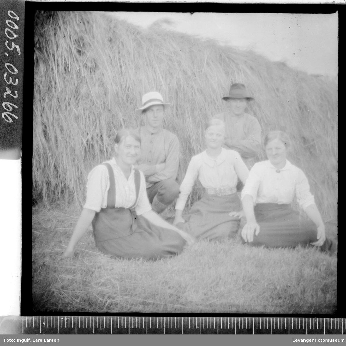 Gruppebilde av tre kvinner og to menn ved en hesjestaur.