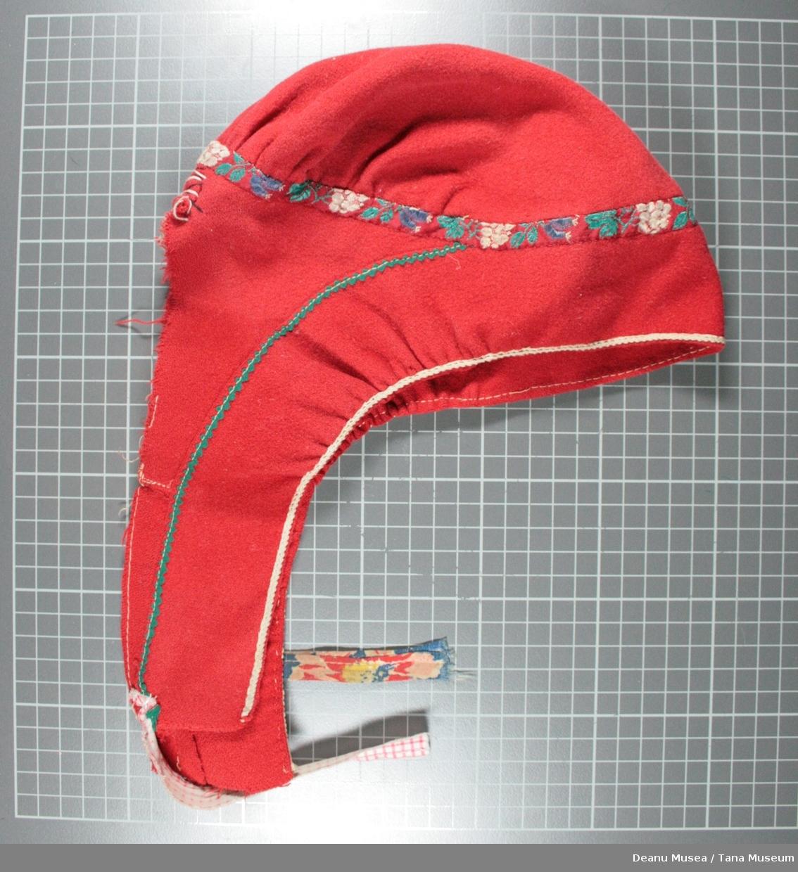 Rød kvinnelue. Dekorert med blomstret silkebånd rundt hode, og grønn sikksakk klede stripe nedover øreflippene.