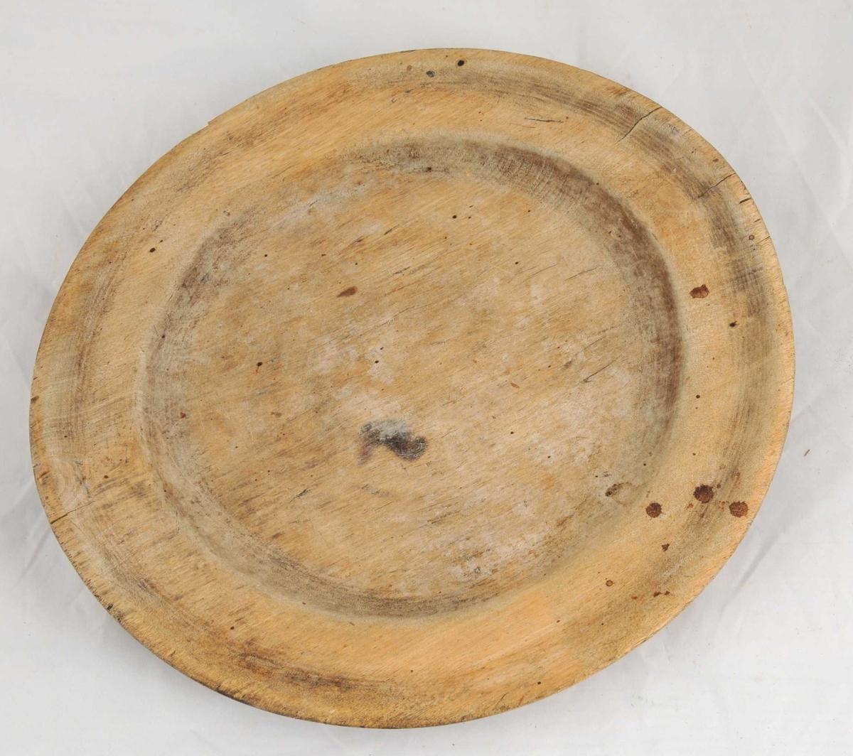 Dreia tallerken, umåla. Innskoren bokstav på undersida.