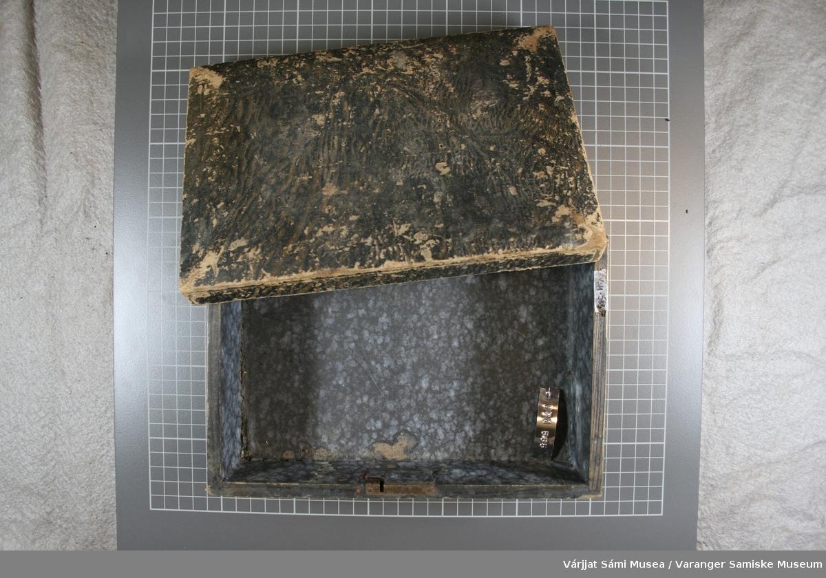 Firkantet treskrin. På innsiden er det trukket med blått/grått papir, yttersiden og lokket er trukket med et mørkt papir med gult mønster. Bunnen er av lyst tre. Lokket har løsnet fra hengslene. På selve skrinet er det to hengsler med bittesmå stiftehull i hver. Skrinet har også  lås, låsen er festet til skrinet med to små stifter Oppå lokket har det vært et håndtak. Man kan ennå se merker etter fire små stiftehull + et rektangulært merke etter beslaget