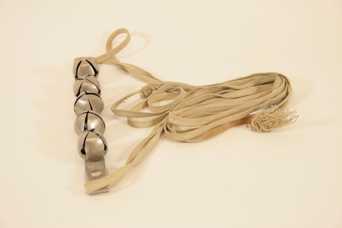 5 stykk dombjeller montert på en flat, grå skinnreim. I endene av reimen er der montert et metallfeste, og en hvit, flat bomullslisse er festet i denne. Reimen er knyttet som en sele.