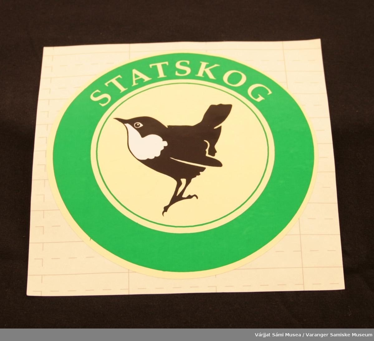 """To runde klistremerker med Statskog logo: Fossekall i midten på lysegul bakgrunn, omgitt av en grønn sirkel med påskriften """"Statskog"""" med lysegule bokstaver."""