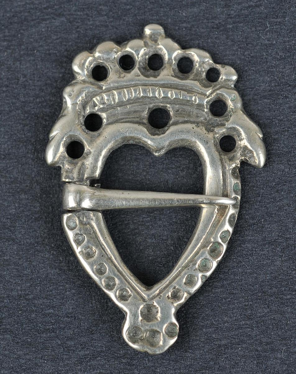 Sprette med motiv av fugl på kvar side av krona. 10 sirkelforma hol i krona.