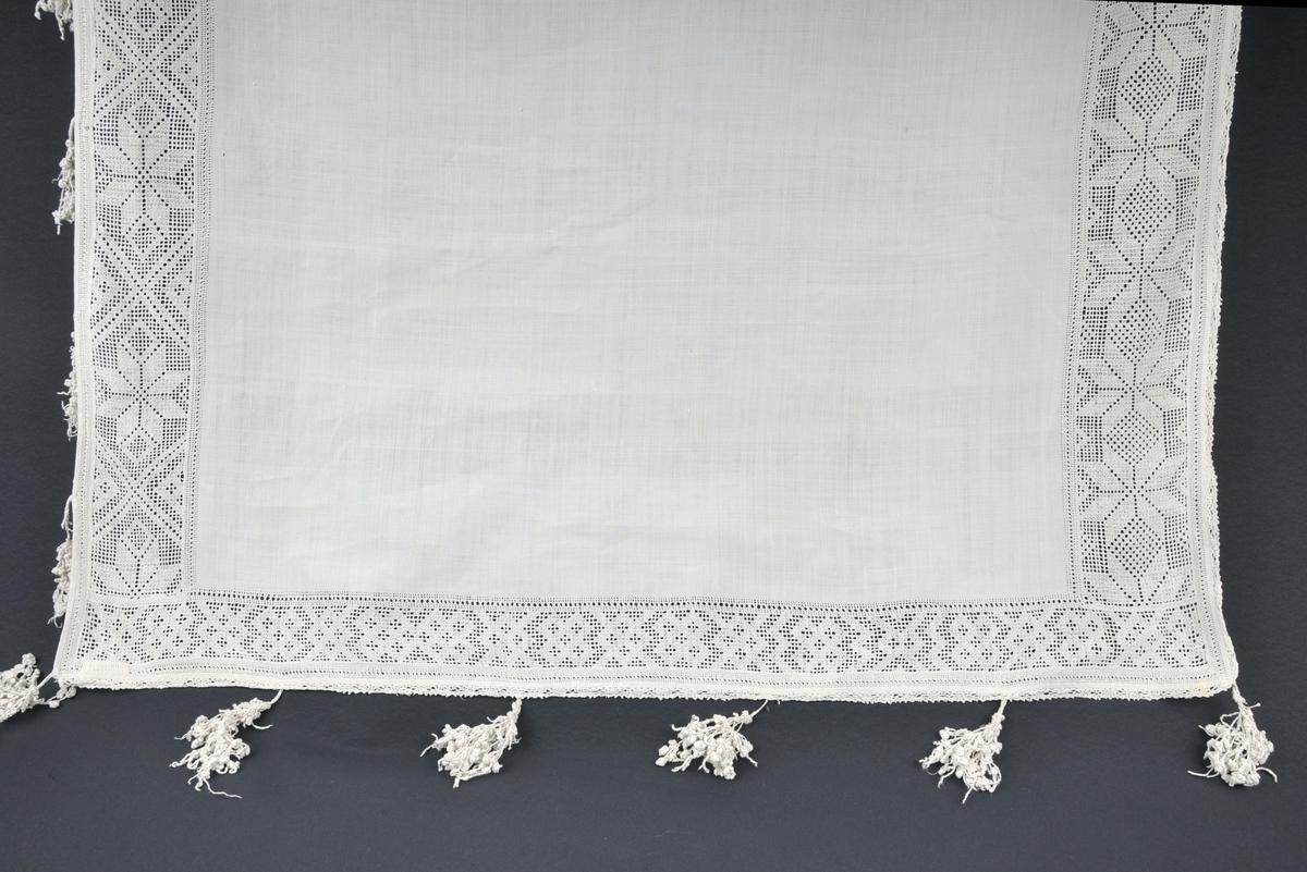 """Rektangulært klede. På langsida ei 10 cm brei bord med uttrekksaum (utskursaum) med 8-bladroser og rutemønster. På dei to stuttsidene: Ei 6 cm. brei bord i same teknikk, men med bare rutemønster. Rundt heile plagget: Ei hekla bord, 1 cm. brei. På kortsidene og eine langsida store dufsar som ifylje Rikard Berge heiter """"skuvar"""", og er utført i ein knyteteknikk i lange strimlar med ei mengd samanknytte kuler. I alt 10 cm lange. Såvidt ein veit er """"skuvar"""" bare bruka på hatteklede."""