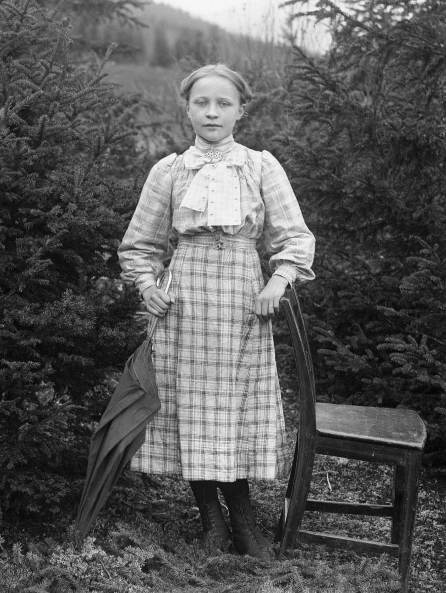 Ung jente kledd i rutete kjole, med kalvekryss/sløyfe i halsen. Stol og paraply som rekvisitter, og skog i bakgrunnen