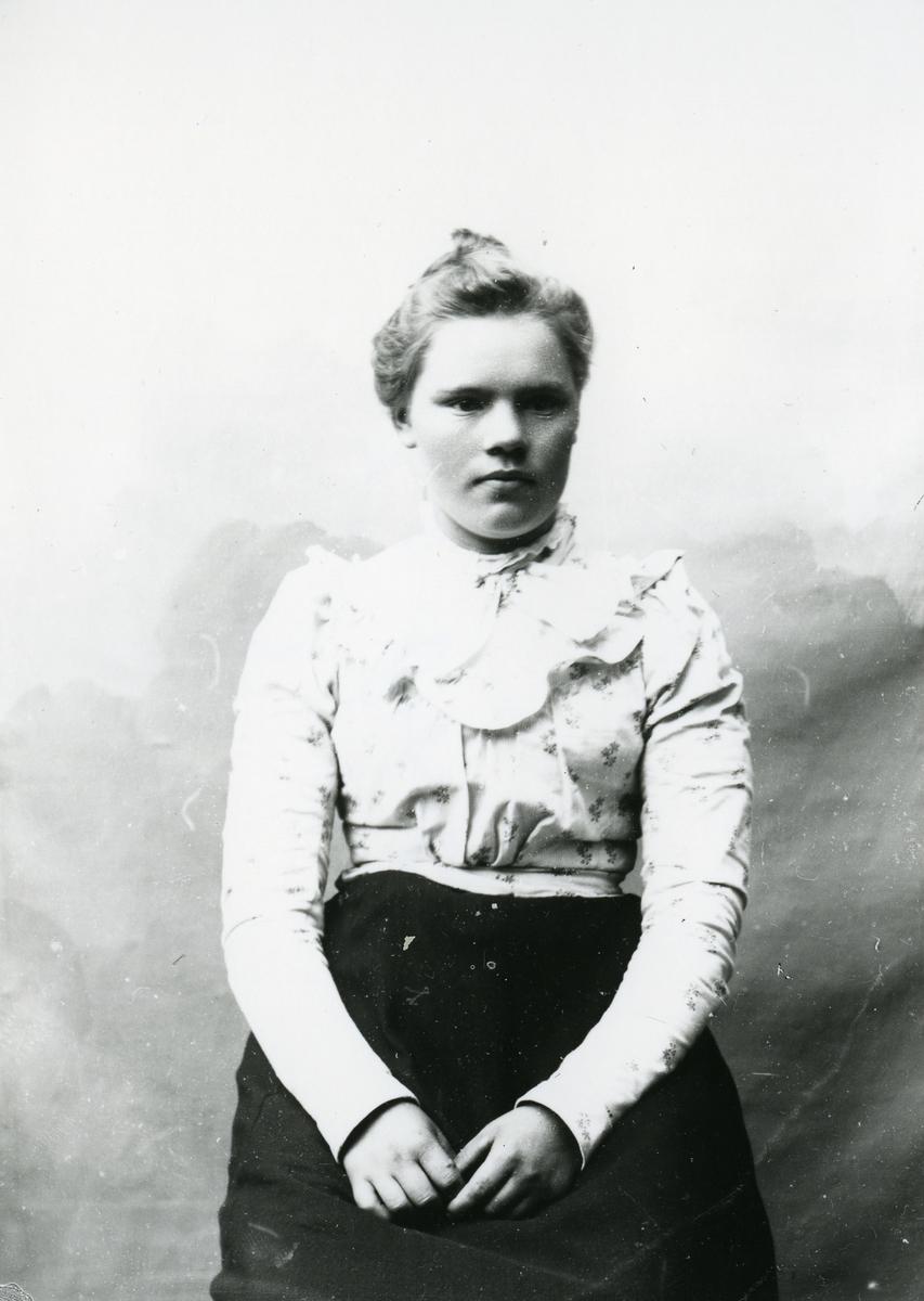 Kvinne kledd i lys mønstrete bluse, i halvfigur, med lerretbakgrunn