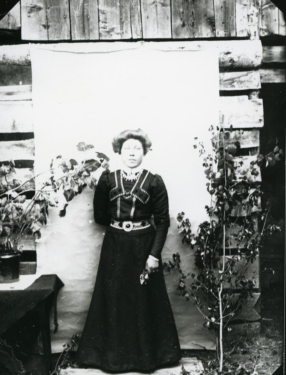 Kvinne i helfigur foran lerret og husvegg